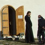 Priester in gesprek met bezoekers van een kerk in Rusland